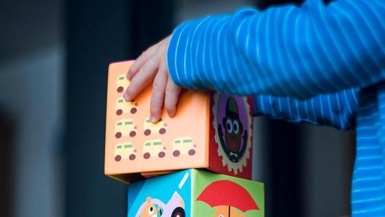Ребенок строит башню из игрушечных кубиков