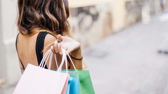 Девушка несет покупки в пакетах