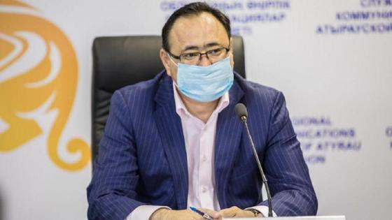 Нурлыбек Кабдыкапаров сидит за столом на мероприятии