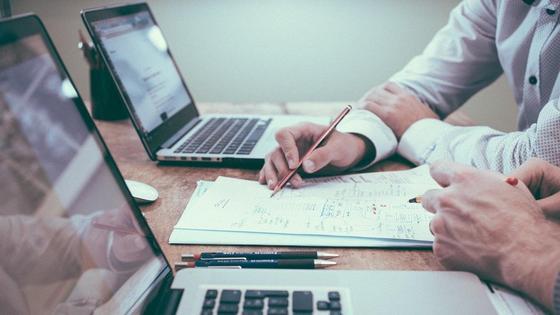 Мужчины пишут на листе рядом с ноутбуками