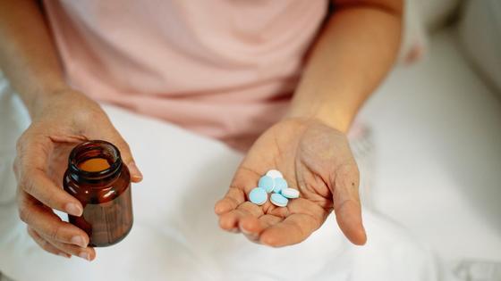 Женщина держит в руках лекарства и бутылек