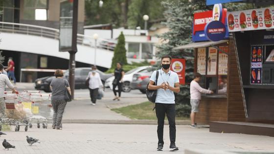 Мужчина в маске идет по улице Алматы