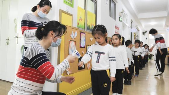Женщина проверяет температуру детей бесконтактным термометром