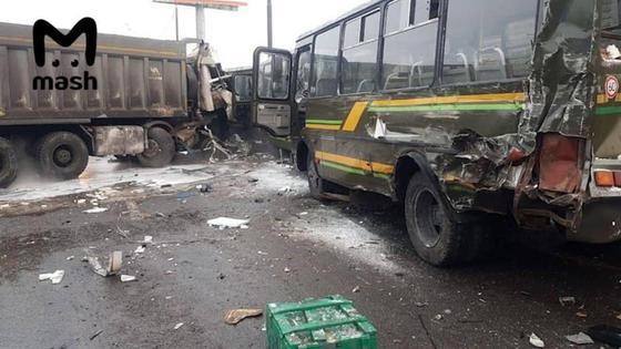 Поврежденные военный автобус и самосвал стоят на дороге