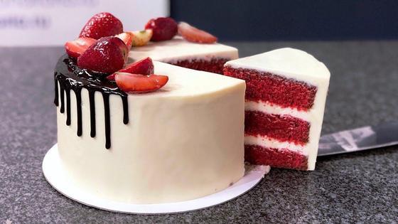 Торт «Красный бархат», украшенный глазурью и клубникой. с отрезанным от него кусочком