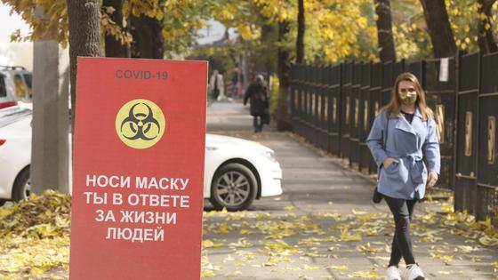 Девушка в маске рядом с билбордом