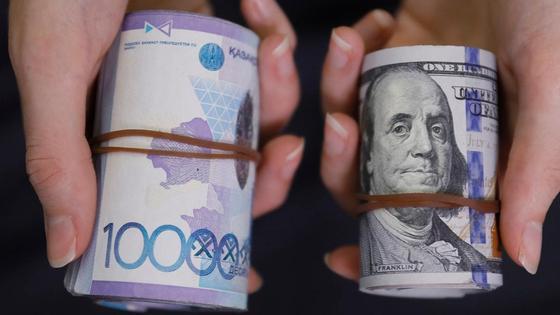 Мужчина держит в руках два денежных свертка