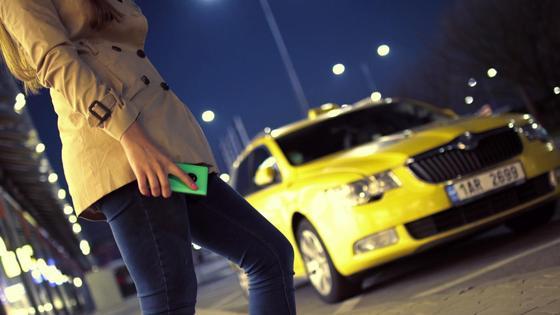Девушка с телефоном в руках стоит на фоне машины такси