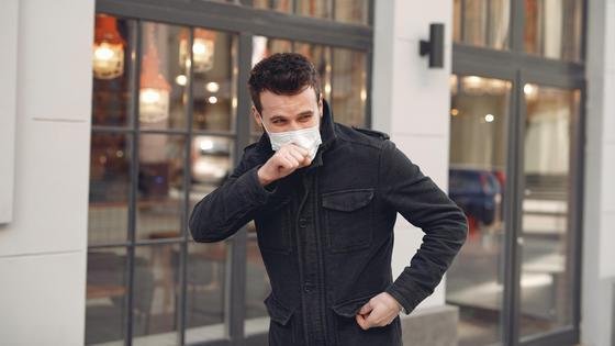 Мужчина в черной куртке и маске кашляет