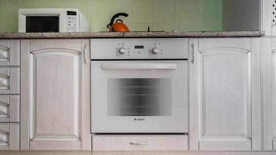 Духовка белого цвета на встроенной кухне
