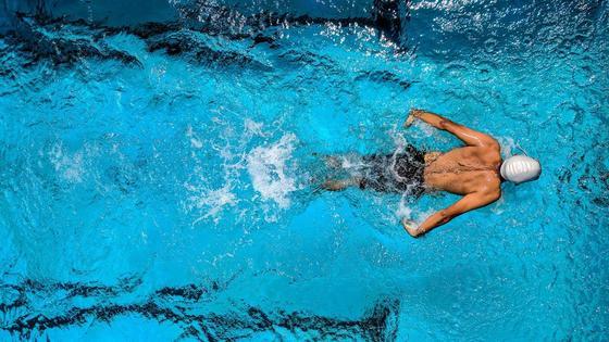 Пловец совершает заплыв в бассейне