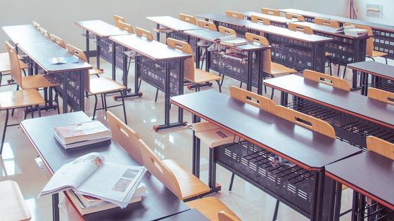 Раскрытые учебники лежат на школьных партах