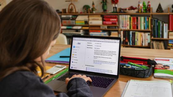Школьница сидит перед включенным ноутбуком