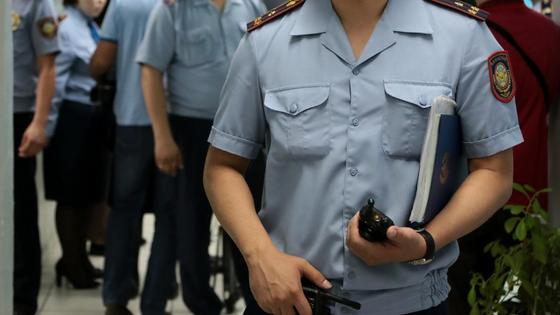 Полицейский в униформе держит в руках рацию