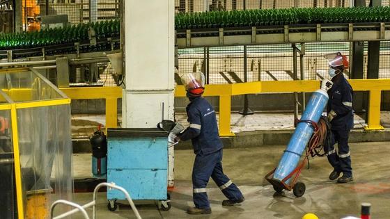 Рабочие в спецодежде перевозят оборудование