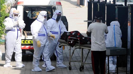 Врачи в защитных костюмах стоят рядом с машиной скорой помощи
