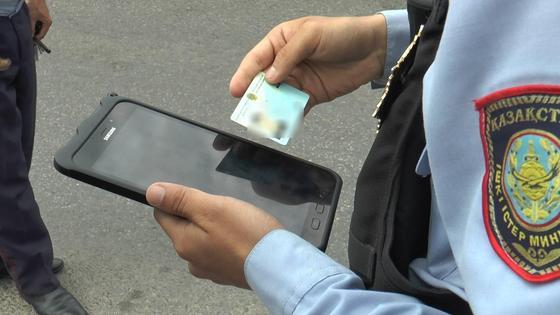 полицейский проверяет документы водителя
