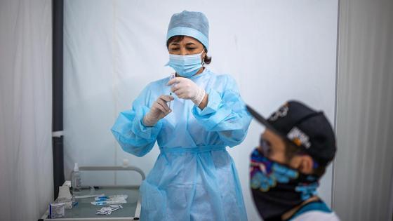 Медсестра готовится поставить пациенту вакцину