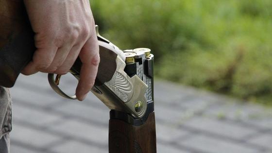 Мужчина держит в руке ружье