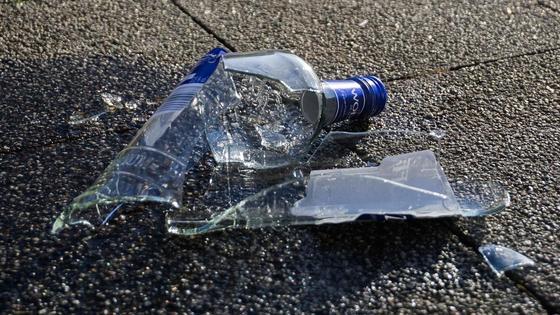 Разбитая бутылка лежит на земле