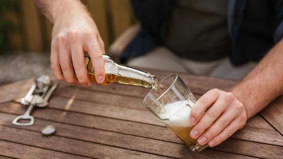 Парень наливает в стакан пиво