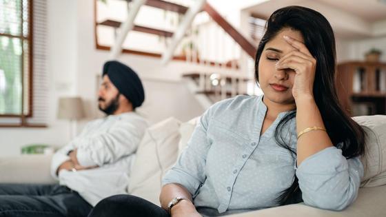 Мужчина и женщина сидят на диване, надувшись друг на друга