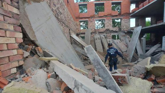 Спасатель ходит в руинах здания