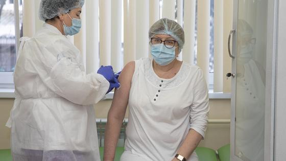 Медсестра делает прививку женщине в очках
