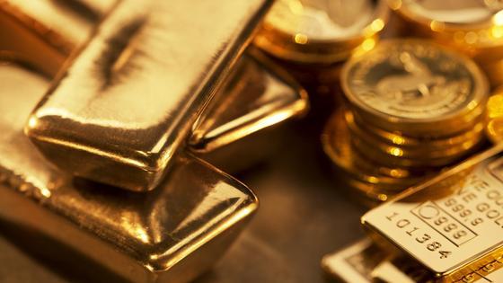 Золотые слитки лежат вместе с золотыми монетами