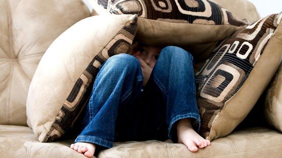 мальчик спрятался под подушками на диване