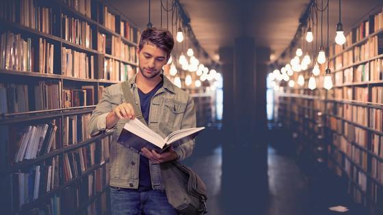 Парень в библиотеке читает книгу