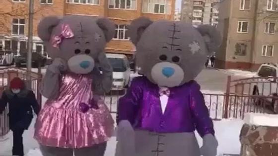 Люди в костюмах мишек Тедди идут по улице