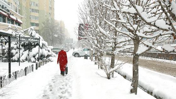 Женщина в красной одежде идет по заснеженной улице
