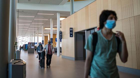 Пассажиры в масках идут по аэропорту