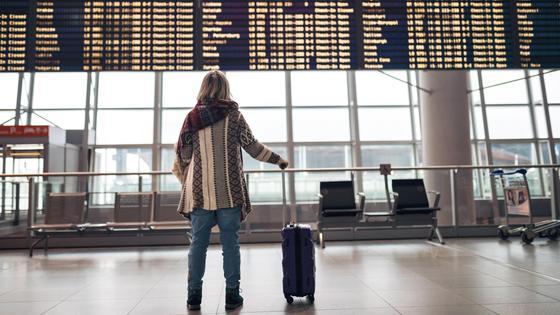 Женщина стоит в аэропорту с чемоданом