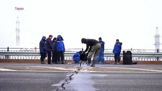 Люди стоят на мосту с трещиной