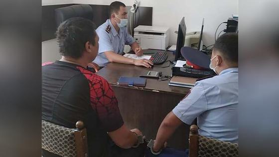 Мужчина в наручниках сидит в кабинете с двумя полицейскими
