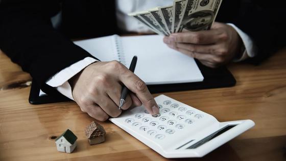 Мужчина держит деньги и использует калькулятор