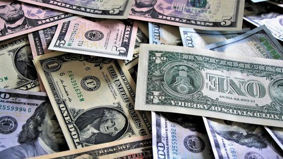 Долларовые купюры хаотично разложены на поверхности