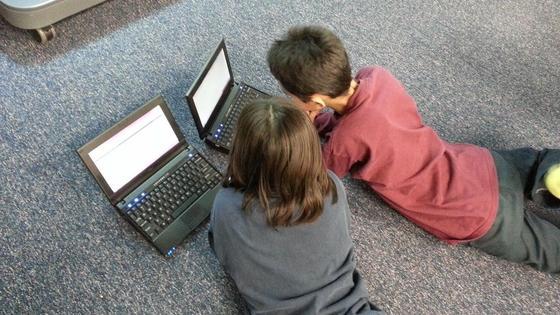 мальчик с девочкой смотрят в экраны ноутбуков