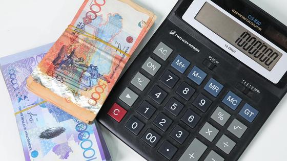 Пачки денег лежат рядом с калькулятором