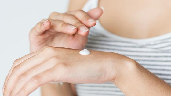 Девушка мажет крем по руке