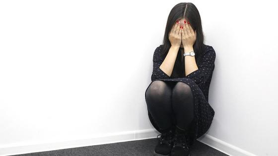 Девушка сидит в углу, закрыв лицо руками
