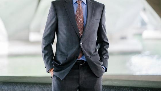Мужчина стоит в строгом костюме