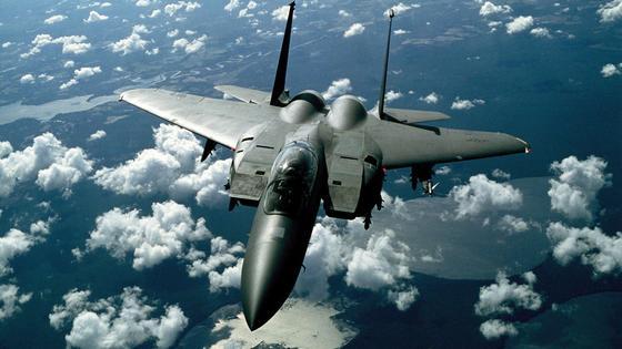 самолет-истребитель летит над облаками