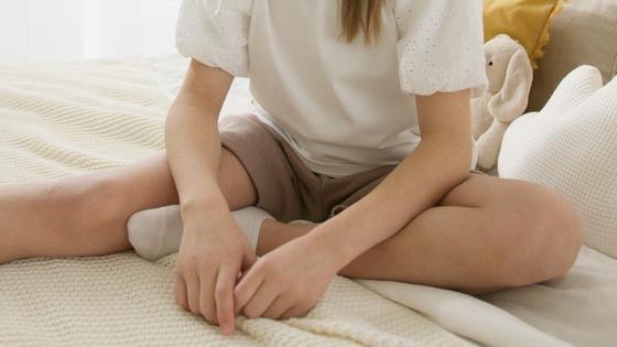 Девочка сидит на кровати