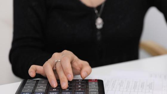 Женщина считает деньги с помощью калькулятора