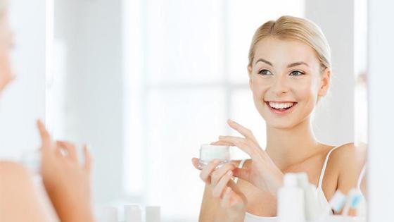 Девушка у зеркала наносит крем