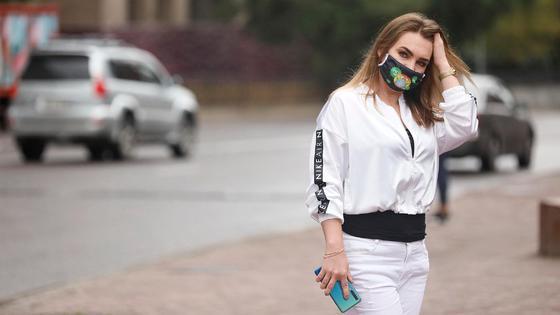Женщина в маске гуляет на фоне машин