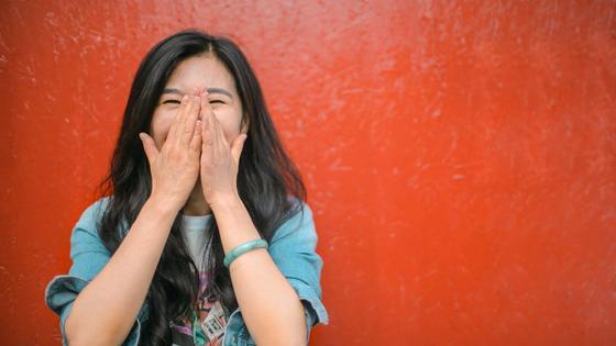 Девушка в джинсовой рубашке закрывает лицо руками на фоне красной стены